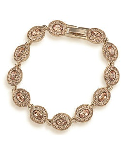 "The Ginny bracelet is a beautiful Topaz and gold tone bracelet. The oval stones are encompassed with smaller stones for a elegant look. Bracelet measures 7"" with a fold over clasp closure. Available in gold tone with Topaz colored stones."
