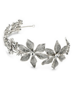 This headband is plated with rhodium silver and is highlighted with two large dazzling floral designs (off to the side) and accented with smaller rhinestone encrusted blooms on either side.