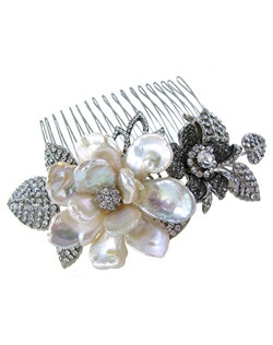 This bridal hair comb may just compete with the real thing. A beautiful flower comprised of freshwater pearl petals surrounded by crystal leaves and flowers to make this comb an ideal accent to any gown. Designed in New York by Regina B.                                                                                                                    Length: 4 1/2"