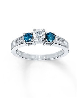 Two round Artistry Blue Diamonds™ set the stage for a sparkling round white diamond center in this 3-stone ring for her. Additional round white diamonds are channel-set in the band of 10K white gold. The ring has a total diamond weight of 3/4 carat. Artistry Blue Diamonds™ are treated to permanently create the intense blue color.