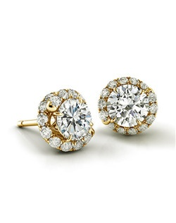 Handmade diamond swirl in yellow gold embracing center diamond.
