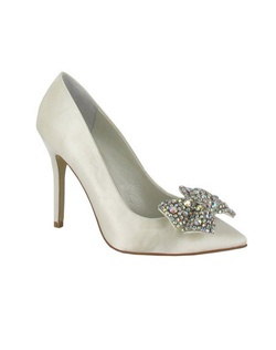 "Looking for a wedding day classic? Check out the Isis by Menbur. A sleek pump toe, perfectly polished with the 4 1/4"" heel. The front is embellished with an over sized bow that is encrusted in various sized and colored rhinestones.Making this bridal pump a perfect mix of pretty and party. Available in Ivory."