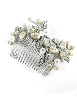 This enchanted comb is comprised of hand carved mother of pearl leaves and flowers accented with Swarovski crystals and pearls. This beautiful combination is sure to turn heads as you walk down the aisle. Unique and feminine. An heirloom in the making!