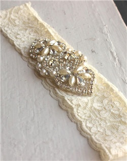 A deco-inspired applique shines with lustrous beading, rhinestones and pearls. Set against delicate cream lace with a soft stretch, this bridal garter is the perfect wedding day keepsake.