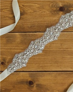 A lustrous rhinestone and pearl encrusted sash is edged with delicate beading. Finished with an ivory satin ribbon, this bridal sash secures neatly with a bow.
