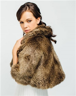 A luxe faux fur cape for those fall and winter weddings. The cape is fully lined, featuring a rolled collar and hidden sleeves for a flattering fit.