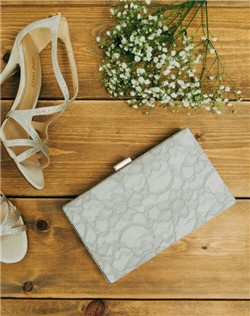 Dove gray lace contrasts a crisp ivory backdrop on this delicate Antoinette Box Clutch. The unique square design is slim enough to slide nicely under your arm while tucking away all those wedding day essentials. A wristlet chain is included, which can be worn inside or out for two looks in one.
