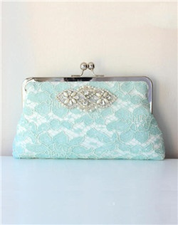 Inspired by old world refinement, a lustrous medallion of intricate beading, rhinestones and pearls adorns delicate mint lace. An exquisite bridal clutch for all those wedding day essentials. Mint lace atop Ivory and gorgeous navy for the lining. A shiny nickel clasp is the finishing touch.