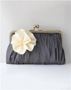 Like a boutonnière tucked into a gentleman's lapel, a delicately ruffled posy graces the exterior of this pleated clutch for the perfect finishing touch.