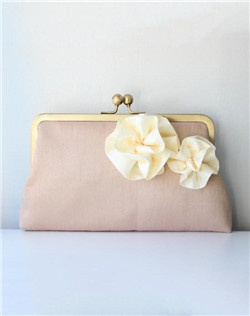 A bouquet of two rosettes is a sweet garnish to this simple clutch. Cream atop champagne and blush for the lining. The brass clasp is the finishing touch.
