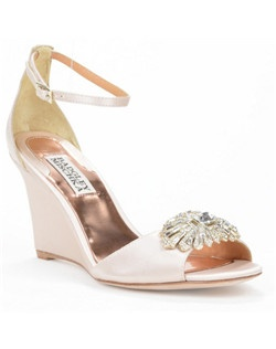 "The Harmony bridal shoe, designed by Badgley Mischka, is a lovely and modern alternative to a traditional open-toe pump, offering instead a sturdier wedge heel. The silk and Natural satin shoe features a 3 1/4"" high wedge that's embellished with a lovely Art Deco-inspired crystal at the toe. An ankle strap adds a touch of femininity."