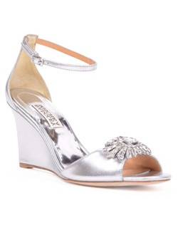 "These stunning metallic wedges from Badgley Mischka, called Harmony-II, feature a 3 1/4"" wedge heel and a pretty ankle strap. The open-toe shoes are embellished with an Art Deco-inspired brooch that adds even more shimmer to the metallic shoes. Wear them at the wedding and beyond!"