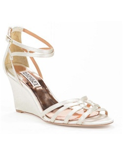 "This delightful wedding shoe from Badgley Mischka, called the Hedy, is a beautiful ivory silk and satin wedge with attractive straps woven at the toe surrounding a pretty open keyhole detail at the top of the foot. An adjustable criss-cross ankle strap offers a measure of comfort and security. The wedges measure 3 1/4"" and are stamped with a decorative textured print."
