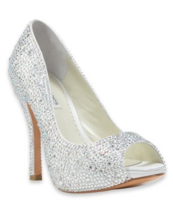 """The Charley shoe, by designer Benjamin Adams, is appropriate for both the bride and her bridesmaids. The white ivory silk shoe is covered with Austrian crystals offering it a shimmer that will look lovely in the light. The peep-toe shoe features a 4 1/2"""" heel."""