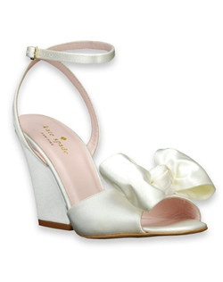 "This elegant open-toe wedge Iberis bridal shoe from kate spade is a gorgeous option that offers both height and simplicity. The ivory satin shoe features a 3 3/8"" wedge and a bow detail at the peep-toe. An ankle strap keeps the shoe in place with the heel exposed. Lovely!"