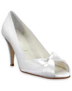 "This elegant bridal shoe from Something Bleu is ideal for a bride who wants a reasonable heel with a few decorative touches. The Caden ivory silk shoe features a lovely criss-cross knotted open-toe with a closed heel and a 3 1/2"" heel."