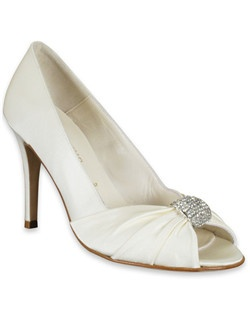 "The Charles shoe from Something Bleu is a glamorous choice for a bride who wants a heel and a little extra sparkle. The ivory silk shoe features a closed heel and an open-toe that's cinched with a lovely rhinestone detail. The tapered, thin heel measures 3 3/4"" and the sole is studded with a blue gem to offer the bride her ""something blue."""
