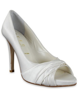 "The Clarke by Something Bleu is a sophisticated option for a bride who doesn't shy away from a little extra height. The ivory silk shoe features an open-toe and a lovely crossover cinched detail with a 4 1/4"" heel. The height is made more comfortable by the interior cushiony platform."