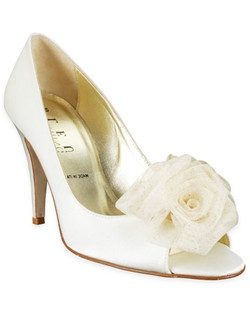 "The Corsage shoe by Something Bleu is a gorgeous shoe for a bride who opts for a touch of flair on her feet. The peep-toe pumps feature a closed heel and a triple-rosette flower decoration that's speckled with gold offering it extra sparkle in the light. A 3 1/2"" heel offers nice height."
