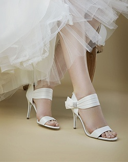 """""""Walk in the room as a true sophisticate and demand attention with an aura of mystery and sensuality in our Cosmos sandal.    • Sandal • Back zipper entry • Crystal brooch • Satin Material • Satin Heel • Available in satin bridal basics: Ivory, silver and champagne  • 4"""""""" Heel • Leather Sole • Imported"""""""