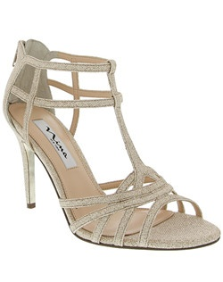 """""""Inspired by the caged elements of the gladiator trend, our City sandal is a light, elegant and a sexy with a hint of sparkle.  Dress up or dress down this silhouette will make heads turn wherever you go!  • T-Strap Sandal • Back Zipper Entry • Bliss Material • Available in Bridal Basics: Silver and Champagne  • 4""""Heel • Leather Sole • Imported """""""