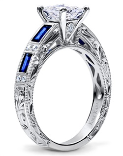 Hand-engraved engagement set from the Kirk Kara Charlotte collection. Engagement ring is crafted with 0.09 carats of diamonds and 0.75 carats of baguette cut sapphires (center stone not included). Shown with matching wedding band crafted with 0.06 carats of diamonds and 0.74 carats of baguette cut sapphires. Available in platinum or 18K white, 18K yellow or 18K rose gold. All Kirk Kara designs are handcrafted and tailored to accommodate your customization requests.