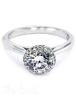 Platinum and diamond solitaire Engagement Ring, pictured with a round brilliant-cut center stone held in place with eight prongs. There are round pave-set diamonds around the center stone and on the shoulders of the ring.  