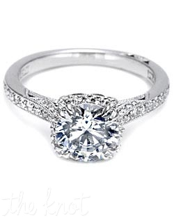 A beautiful juxtaposition of modern, yet traditional; classic, yet unconventional. This stunning ring features a round center stone with diamond enhancers blooming the stone.  This gorgeous setting is also available in Medium and Grande proportions; with pave shoulders; as a three-stone ring; or with Oval, Emerald or Princess centers.