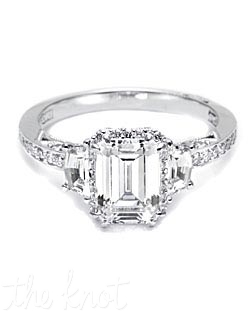 A beautiful juxtaposition of modern, yet traditional; classic, yet unconventional. This ring features an Emerald center stone with Cadillac-cut side stones and diamond enhancers blooming the stone.  This setting is also available in Medium and Grande proportions; without pave shoulders; solitaire ring with Oval, Round or Princess centers.