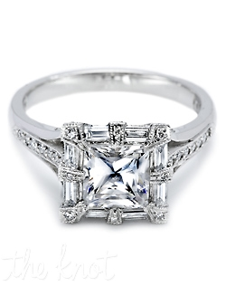 Platinum and diamond Solitaire Engagement Ring, pictured with a princess-cut center stone surrounded by baguette and round pave-set diamonds which continue down the shoulders of the band.