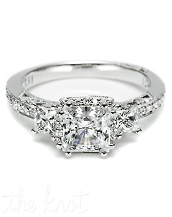 A beautiful juxtaposition of modern, yet traditional; classic, yet unconventional. This stunning ring features a princess center stone with diamond enhancers blooming the stone, flanked by princess side stones and pave diamond shoulders. This gorgeous setting is also available in Petite or Grande proportions and without pave shoulders.