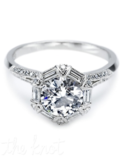 Platinum and diamond Solitaire Engagement Ring, pictured with a round brilliant-cut center stone surrounded by baguette and round pave-set diamonds which continue down the shoulders of the band.  This setting is also available in Larger proportions.