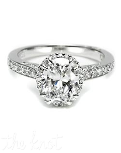 For a woman with an eye for glamour, this ring is sublime. Round diamonds encircle an oval center stone with diamonds both along the shoulders and on the sides, for lustrous shine from all angles. Matching band style is 2630 B SM 1/2.