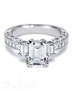 Brighten an emerald-cut diamond with two emerald-cut side stones and a milligrain-accentuated shining, streamlined band of channel-set princess-cut diamonds. The sides of the band are finished with signature crescent silhouette diamond details.