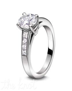 Round center stone set into Platinum, surrounded by channel set princess cuts, from our Nikole Collection.  The matching band, R-3102/B is not shown, but lines up end to end with this ring to make a very elegant bridal set.  100% hand crafted in the USA, .35ct total weight. Also available in white gold and yellow gold.