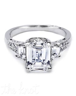 Step it up with a unique and bold emerald-cut solitaire with two trapezoid-shaped side stones. The high-polished knife edge band is set with dazzling rows of pave. Matching band is style 2520 ET.