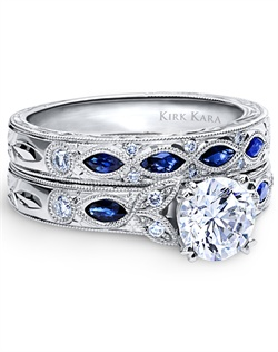 Hand-engraved engagement set from the Kirk Kara Dahlia collection. Engagement ring is crafted with 0.12 carats of diamonds and 0.22 carats of marquise cut sapphires (center stone not included). Shown with matching wedding band crafted with 0.08 carats of diamonds and 0.35 carats of marquise cut sapphires. Available in platinum or 18K white, 18K yellow or 18K rose gold. All Kirk Kara designs are handcrafted and tailored to accommodate your customization requests.