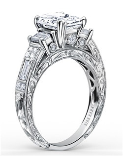 Award winning design. This deco inspired classic is a three stone engagement ring from the Charlotte collection. It features 0.85 ctw of diamonds. The signature handcrafted details include scroll hand engravings, milgrain edging and peek-a-boo diamonds. The center 1.5 carat emerald cut stone (shown) is a customized option. Engagement ring is also available as shown featuring blue sapphires (K1384SDE-R) or pink sapphires (K1384VDE-R). Matching wedding band is also available as shown featuring all diamonds (SS6685D-B), blue sapphires (SS6685-B1), or pink sapphires (SS6685P-B1).