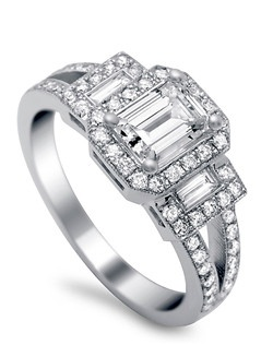 Brilliant round diamond halo surround the spectacular emerald cut center stone. Additional .52 ct TW brilliant round diamonds line split shank and surround halo.