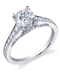 18k white gold engagement ring with a 1ct round brilliant center diamond. 0.49 total carats of tapered round brilliant diamonds flow down the channel shank and inside shank.