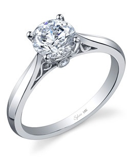18k white gold engagement ring with a 1ct round brilliant center diamond. The round brilliant diamonds inside the shank, below the center total 0.03 carats.