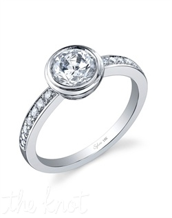 18k white gold engagement ring with a 1ct round brilliant center diamond. The round brilliant diamonds flowing down the channel shank total 0.16 carats.