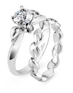 A brilliant round diamond elegantly emerges from blooming satin-brushed leaves.  Shown with Parade Design's original Lyria® Leaves wedding band featured in the 2012 release of The Vow, starring Rachel McAdams! Satin finished cascading leaves  are crafted in the finest 18K gold. Lyria® strikes a balance between strength and beauty, symbolizing a union that will last a lifetime. Available in platinum, 18K white, 18K yellow, 18K rose gold or palladium. All Parade Design styles can be customized upon request.