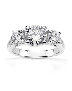 Trellis setting three stone diamond engagement ring also furnished with channel set diamonds on the shank. This stunning engament ring features sparkling 0.94 ct. tw round diamonds. Center can be set with 0.65 ct. - 0.85 ct. round diamond range. Setting is available in 14k, 18k gold, platinum and palladium.