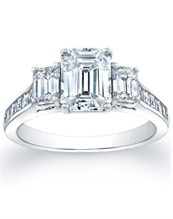 This gorgeous three stone engagement ring setting features two emerald cut side diamonds totaling approx .64ct. In addition the setting has square emerald-cuts that are channel-set and go half way around the band. This setting is designed to fit flush with just about any wedding band.