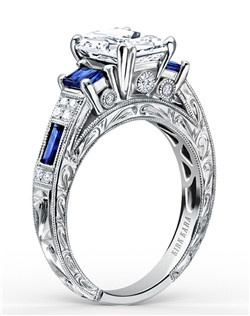 Hand-engraved engagement set from the Kirk Kara Charlotte collection. Engagement ring crafted with 0.11 carats of diamonds and 1.34 carats of blue sapphires (center stone not included). Shown with matching wedding band crafted with 0.06 carats of diamonds and 0.74 carats of baguette cut sapphires. Available in platinum or 18K white, 18K yellow or 18K rose gold. All Kirk Kara designs are handcrafted and tailored to accommodate your customization requests.