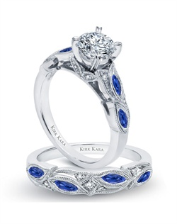 Handcrafted engagement set from the Kirk Kara Dahlia collection. Engagement ring crafted with 0.04 carats of diamonds and 0.43 carats of marquise cut blue sapphires (center stone not included). Shown with matching wedding band crafted with 0.03 carats of diamonds and 0.39 carats of marquise cut blue sapphires. Available in platinum or 18K white, 18K yellow or 18K rose gold. All Kirk Kara designs are handcrafted and tailored to accommodate your customization requests.