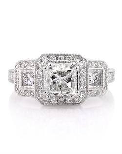 This remarkably beautiful princess cut diamond engagement ring combines excellence in design, craftsmanship and quality! The 1.50ct princess cut diamond set in the center is EGL certified at G-VS1, perfectly white and clear, even under 10X magnification. It is accented by a halo of round diamonds in a pave setting. There are two large and beautiful princess cut diamonds accenting it on its sides with a halo of round diamonds set around them as well. The shank is pave set with round diamonds on all three sides. The center basket is so unique and beautiful with gorgeous filigree detail and a small round diamond set in the center basket. This piece is extraordinary in so many ways! You will love it!