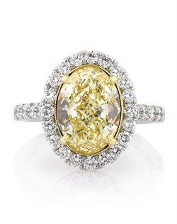 This magnificently beautiful and very rare fancy yellow oval cut diamond ring will astonish you with its exceptional color, quality and brilliance! The exceptional 3.70ct oval cut diamond set in the center is GIA certified at Fancy Yellow VS2. It has a very vibrant and rich yellow color and it is very clear, even under 10X magnification. It is very hard to find oval cut diamonds as beautifully cut, brilliant, and amazing as this one, especially in this weight range! We custom made this stunning setting to showcase it beautifully. It features a halo of round diamonds set around it and one row of round diamonds set down the shank in a micropave setting. The diamonds stand out perfectly with hardly any metal showing. The center basket is made in 18k yellow gold with gorgeous handmade engraving throughout. It is accented by sparkly round diamonds set all along the connectors. It is such a work of art! You will be mesmerized when you see this stunning piece in person. One in a million!