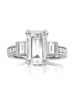 This breathtaking emerald cut diamond ring is one of a kind! This magnificent piece features a mesmerizing 3.29ct emerald cut diamond in the center. It is GIA certified at G-VS1, perfectly white and perfectly clear, even under 10X magnification! The cut is outstanding! It looks more like a four carat emerald cut diamond! It is flanked by two large emerald cut diamonds that accent it perfectly. The shank is pave set with round brilliant cut diamonds on all three sides. The center basket is incredibly unique and beautiful! It features two gorgeous carre cut diamonds, channel set in the center and has round diamonds pave set around it and on the center prongs. This remarkable work of art it astonishing in every way! This piece is sure to become a family heirloom. You will cherish it forever!